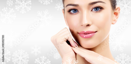 Pretty woman against a grey background with copyspace and snowflakes