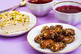 Oriental sweets-halva and dates on bright pink background