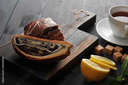 Staande foto Klaprozen roll with poppy seeds, tea, lemon and mint on wooden background