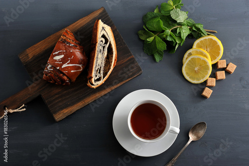 roll with poppy seeds, tea, lemon and mint on wooden background