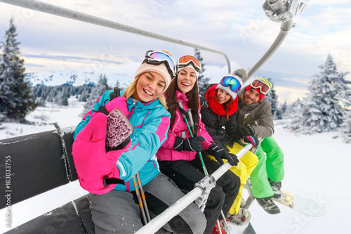 cheerful friends skiers enjoying in the slopes at winter vacations and making selfie