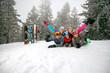 cheerful skiers lying on snow and having fun
