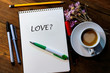 album, pens and pencils on a wooden table. a cup of coffee with milk. inscription - love.
