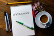 album, pens and pencils on a wooden table. a cup of coffee with milk. inscription - I feel good.