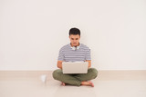 Casual asian man sitting on floor using laptop at home in the living room - 183049742