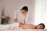 Woman's body on the acupuncture - doctor sticks needles, close up