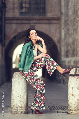 Plakát Young brunette woman smiling in urban background.