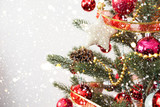 Close-up of Christmas tree with ornament, decoration and light bokeh with snowfall on winter background - 183058389