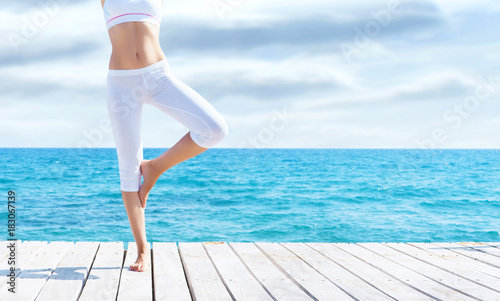 Attractive girl in white sporty clothes doing yoga on a wooden pier. Yoga, sport, leisure, recreation and freedom concept.