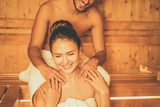 Young happy couple relaxing inside a sauna at spa resort hotel luxury - Romantic lovers having a bodycare day in steam bath man making a massage for his girlfriend - Relax, love, lifestyle concept - 183078193
