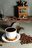 A White Cup of Hot Coffee in a Scattering of Coffee Beans on a Wooden Background - 183078378
