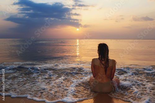 a girl meditating on the ocean shore Poster