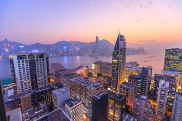 Spectacular aerial view of Victoria Harbor, skyscrapers and Hong Kong skyline at night.