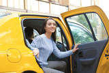 Fototapety Young woman getting out of taxi car