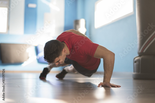 Young man trains push-ups in the gym on one hand indoors