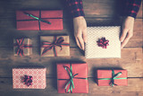 woman's hands holding packed gift box on old wooden table. top view