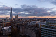 Elevated aerial view of modern London cityscape skyline rooftops at sunset with clouds