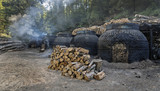 The production of charcoal in a traditional manner in the forest - 183100589