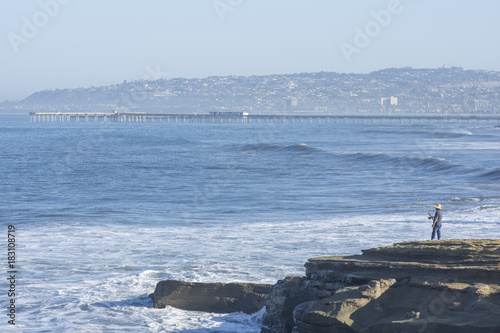 Ocean Beach pier and man fishing on rocky shore Poster