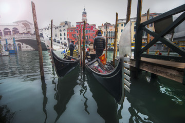 Gondoliers in gondolas at a canal in Venice with Rialto bridge in the background.
