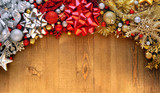 Christmas bows, ornaments, and decorations on wooden background - 183110300