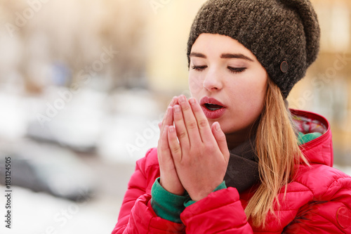 Woman during winter warming up her hands