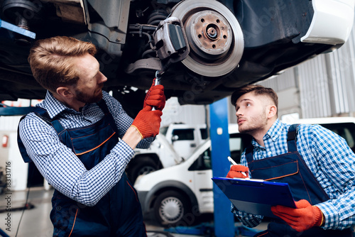 Father and son work at the auto service. Two mechanics work with the details of the car. - 183131716