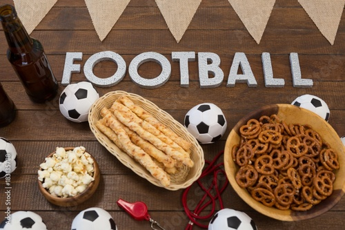 Football text and snacks on wooden table