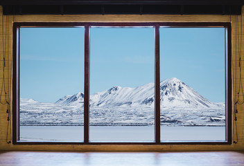 Looking through window in winter, wooden window frame with desk and landscape snow mountain and frozen lake view in Iceland