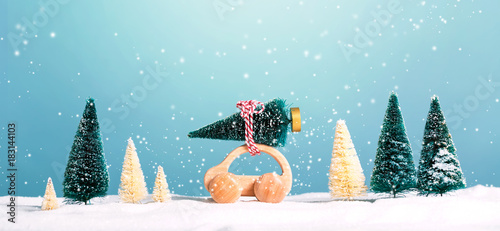 Miniature wooden car carrying a Christmas tree on a blue background - 183144103