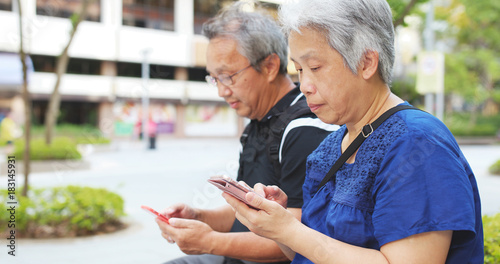 Retired couple using mobile phone together
