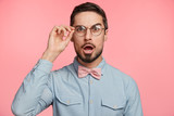Surprised male manager stares through spectacles, keeps jaw dropped, shocked to see that there isn`t anyone on work place, tries to control work of colleagues. Amazed bearded young businessman - 183156781