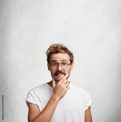 Vertical portrait of puzzled fashionable male with trendy hairstyle frowns face in bewilderment, keeps hand on chin, bites lower lip, can`t understand something, isolated over white background