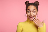 Excited young black female looks in bewilderment at camera, being pleasant surprised by information about her victory of competition, can`t belive in this, pose against pink background with copy space - 183157151