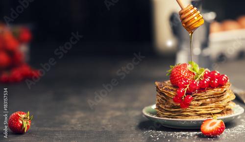 Homemade pancakes with fresh berries and honey