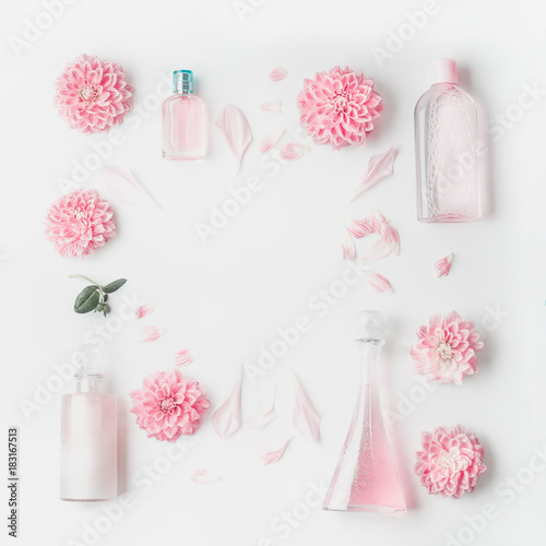 Pastel pink cosmetic product setting flat lay with flowers on white desk background, top view, frame. Layout for skin care, wellness or spa and beauty concept