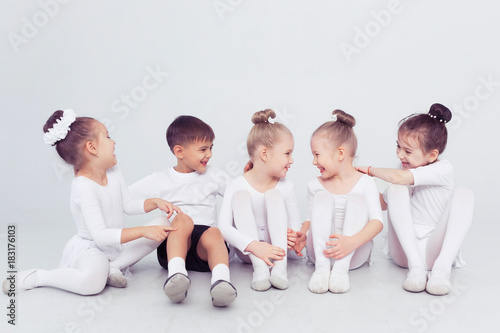 Group of kids boys and girls dancing at a white class room or studio smiling and hugging together