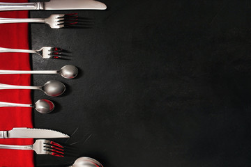 silver cutlery set on black background with red color accents. Table setting for banquet concept