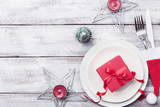 Christmas table setting. Gift box, fir tree, white plate and silverware on rustic table top view. Preparation for holiday dinner. - 183191704