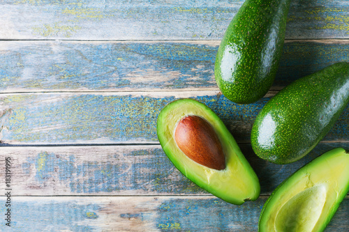 Half and whole avocado on vintage wooden table top view. Organic wellness food background. Copy space.