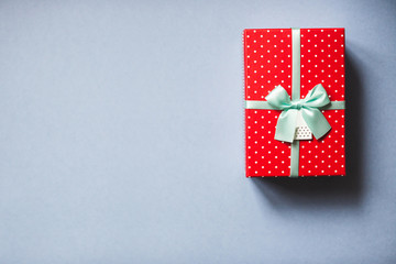 Packed red present with bow on blue background.