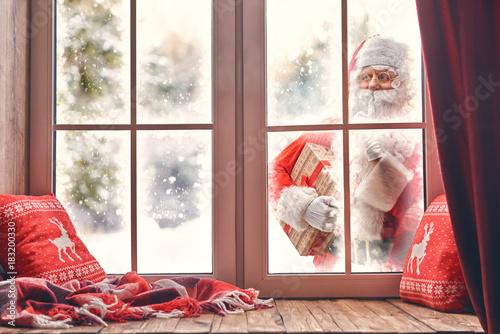 Santa Claus is knocking at window - 183200330