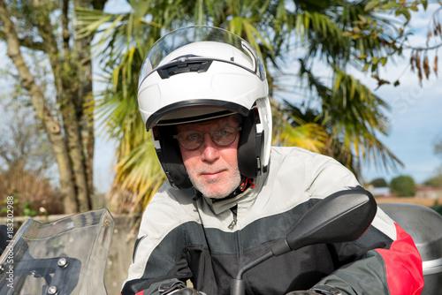 portrait of a senior biker on his motorcycle