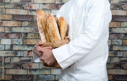 baker holding traditional bread french baguettes