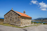 Historic village medieval church by the asphalt road during sunny day, blue sky - 183203718