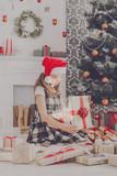 Beautiful girl in santa hat unwrapping christmas presents - 183204155