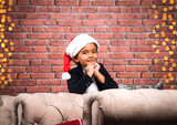 cute little Indian boy looking at camera with red santa hat and smiling with hands on chin 