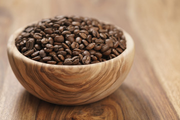 fresh roasted coffee beans in wood bowl on table