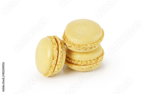 three yellow lemon macarons isolated on white