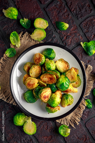 Foto op Aluminium Brussel Homemade Roasted Brussel Sprouts with Salt, Pepper on a old stone rustic table.